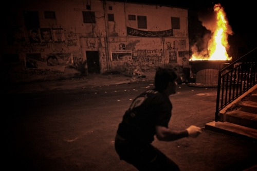 fotojournalismus:  A Shiite protester throwing Molotov cocktails towards riot police, who fired tear gas and birdshot in response, during clashes following a demonstration in Sitra on August 14, 2012. Bahrain's Shiites complain they have long been marginalized in political and economic life, which the government denies. But there has been no progress on the main opposition demand for a parliament with full powers to legislate and form governments. Bahrain's Sunni rulers have rejected opposition calls for an elected government, and protests and clashes with police continue. [Credit : Mohammed Al-Shaikh / AFP / Getty Images]