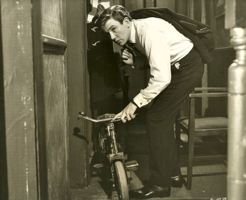 "Albert Finney rights a bike. Snipe: ""Arthur Seaton (Albert Finney) accidentally knocks over a child's bicycle as he surreptitiously leaves the home of his workmate, with whose wife he is having an affair."""