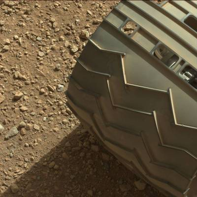One of Curiosity's wheels with some Mars under them.