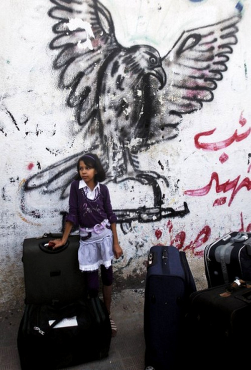 A Palestinian girl waits on the Palestinian side of Rafah before crossing the border between southern Gaza Strip and Egypt, Tuesday, Aug. 14, 2012. Egypt on Tuesday opened its border with Hamas-ruled Gaza for a three-day period ahead of a major Muslim holiday, but imposed tight restrictions on who can travel and did not say whether it would resume normal border operations. (AP Photo/Hatem Moussa)