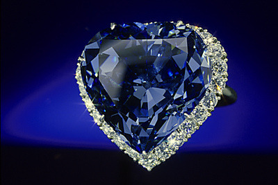 The remarkable Blue Heart Diamond was found at the Premier Mine, South Africa in 1908. This 30.62 carat heart-shaped, brilliant cut blue diamond was faceted by French jeweler Atanik Eknayan of Paris in 1909-1910 from a 100.5 carat piece of rough. The stone was purchased by the French jeweler, Pierre Cartier in 1910. Cartier then sold it to a Mrs. Unzue of Argentina in a lily-of-the-valley brooch in 1911. It was next acquired by Van Cleef & Arpels in 1953 and sold to a European family in the form of a pendant. In 1959, it was purchased by Harry Winston who mounted it in its present platinum ring setting, surrounded by 25 round brilliant cut colorless diamonds with a total weight of 1.63 carats. The Blue Heart Diamond is approximately 2/3 the size of the Hope Diamond, but its heart-shaped brilliant cut and lively blue color have made it one of the collections most popular gems. The Gemological Institute of America (GIA) graded the Blue Heart as a natural fancy deep blue diamond with a clarity grade of VS-2.