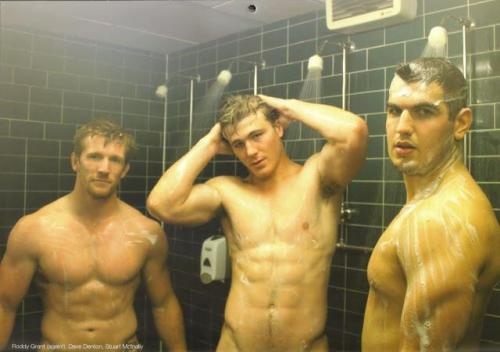Three team mates showering together after a game.