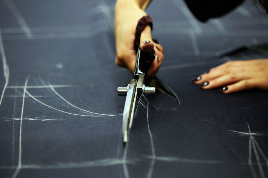 An employee cuts up a piece of cloth in the workshop at the Gieves & Hawkes store, owned by Trinity Ltd., on Savile Row in London, on Aug 7. Photograph by Chris Ratcliffe/Bloomberg