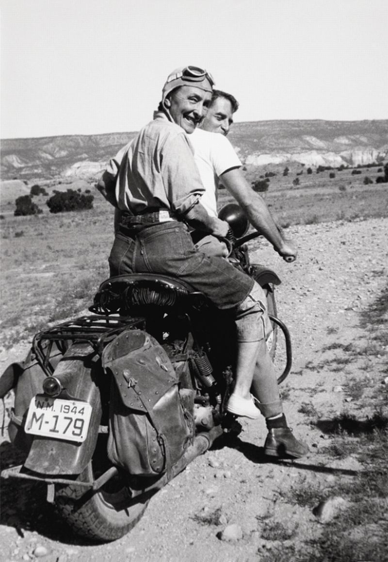 """Georgia O'Keeffe hitching a ride to Abiquiu, Ghost Ranch, 1944″ AKA ""Women Who Rode Away."" –Image by Maria Chabot @Georgia O'Keeffe Museum. The painter, Maurice Grosser, visited his friend O'Keeffe's ranch in 1944. Maria Chabot photographed O'Keeffe and Grosser on his 1938 Harley-Davidson Knucklehead. It's an amazing image that celebrates denim, machine, and the joy of the open road. That look on O'Keeffe's face says it all."