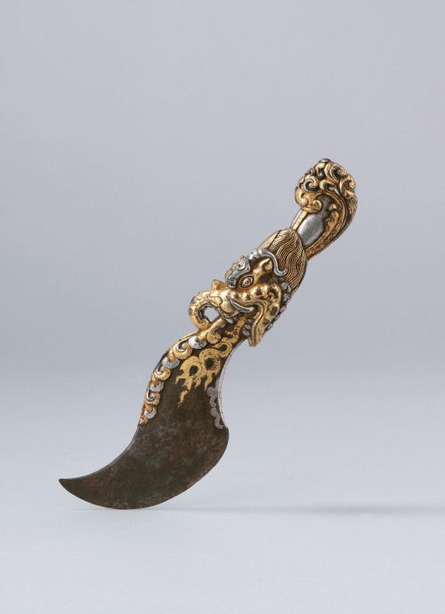 art-of-swords:  Vajra Water Knife Date: ca. 15th century Culture: Tibet Medium: Iron damascened with gold and silver Dimensions: H. 9 1/2 in. (24.1 cm); W. 2 7/8 in. (7.3 cm) Classification: Metalwork Credit Line: Lent by Anthony d'Offay Rights and Reproduction: Photograph © Rossi & Rossi A wavelike steel blade emitting from a makara (sea monster) and a wave-form hilt earned this blade the title Vajra Water Knife (Tibetan: dorjey chutri). The makara has an elephant's trunk and tusks, which are bizarrely paired with the jaws of a crocodile and the flowing mane of a lioness. The traditional Indian makara of antiquity has an aquatic tail, which here, filtered through the Tibetan imagination, has become a great foaming wave. A variant of the traditional flaying knife (Tibetan: triguk), this blade is a masterpiece of gold and silver workmanship. The contrasting metals damascened into the iron surface create a ritual utensil of threatening beauty.  Source: Metropolitan Museum of Art