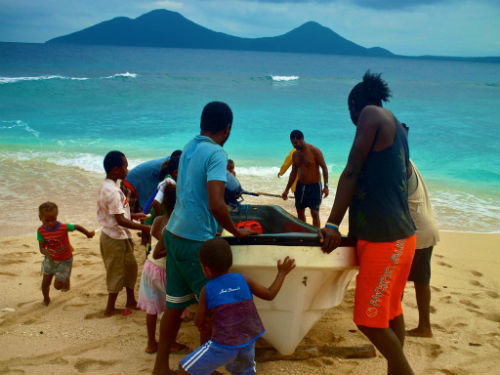 Members of Peace Corps Volunteer Stephanie Bergado's small island community pull the boat used to access their local health center boat to shore.