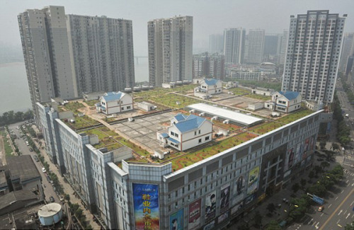 "nickkahler:  Mutant Urban Suburbanism, Zhuzhou, China, c. 2012 (via architizer) ""The Chinese city of Zhuzhou, the second largest in the province of Hunan, is being pressed under the tremendous pressure of growth. Home to many a manufactory and textile mill, residents are seeking new ways to live close to work while preserving the spaciousness of the countryside. Thus, these wonderful photos of McMansion-style housing atop a five-story shopping center in the central district of Zhuzhou. The four houses are perched above the city, invisible to street-level action. They do not cast a shadow on the ground, and seem to exist solely in the rarefied world of smoggy skies, with scenic views into the apartments surrounding their airy enclave. Though the landscaping around the houses leaves something to be desired, the overall approach is one we'd like to see replicated on blank and bare urban roofscapes everywhere. Now that's mixed-use development."""