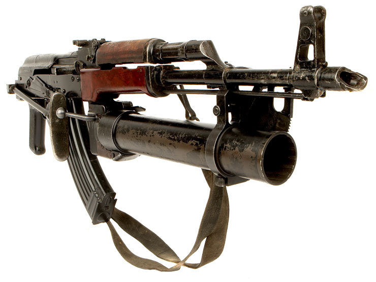 "AK Grenadier Very interesting rifle with a rather uncommon Polish Pallad 40mm Grenade Launcher. The rifle itself looks like it might be an Egyptian but with different handguards. I say Egyptian because of the ""crutch"" style side-folding stock. The East Germans had the same style but they never painted theirs in the black enamel finish that the Egyptians preferred. Without any larger images I can't be 100% certain as to what mix of parts this rifle has. Sadly this one is a deactivated gun, no longer capable of firing."