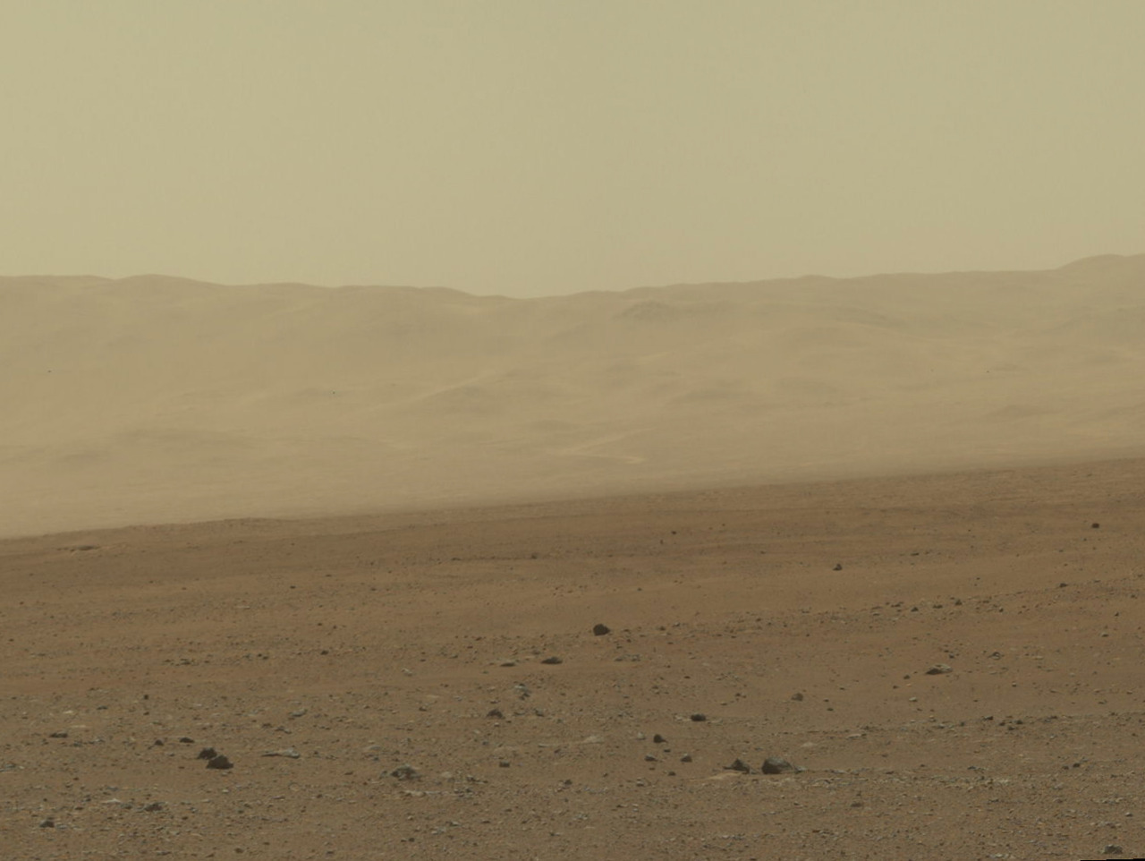 Wall of Gale Crater of Mars, photo taken by NASA Curiosity Rover This color image from NASA's Curiosity rover shows part of the wall of Gale Crater, the location on Mars where the rover landed on Aug. 5, 2012 PDT (Aug. 6, 2012 EDT). This is part of a larger, high-resolution color mosaic made from images obtained by Curiosity's Mast Camera. This image of the crater wall is north of the landing site, or behind the rover. Here, a network of valleys believed to have formed by water erosion enters Gale Crater from the outside. This is the first view scientists have had of a fluvial system - one relating to a river or stream — from the surface of Mars. Known and studied since the 1970s beginning with NASA's Viking missions, such networks date from a period in Martian history when water flowed freely across the surface. The main channel deposit seen here resembles a dirt road ascending into the mountains, which are actually the north wall and rim of Gale Crater.   Although Curiosity is about 11 miles (18 kilometers) away from this area and the view is obscured somewhat by dust and haze, the image provides new insights into the style of sediment transport within this system. Curiosity has no current plans to visit this valley system, since the primary objective of the rover is south of the landing site. But images taken later and with the 100-millimeter Mastcam are likely to allow scientists to study the area in significantly more detail.  The images in this mosaic were acquired by the 34-millimeter MastCam over about an hour of time on Aug. 8, 2012 PDT (Aug. 9, 2012 EDT), each at 1,200 by 1,200 pixels in size.  Image credit: NASA/JPL-Caltech/MSSS