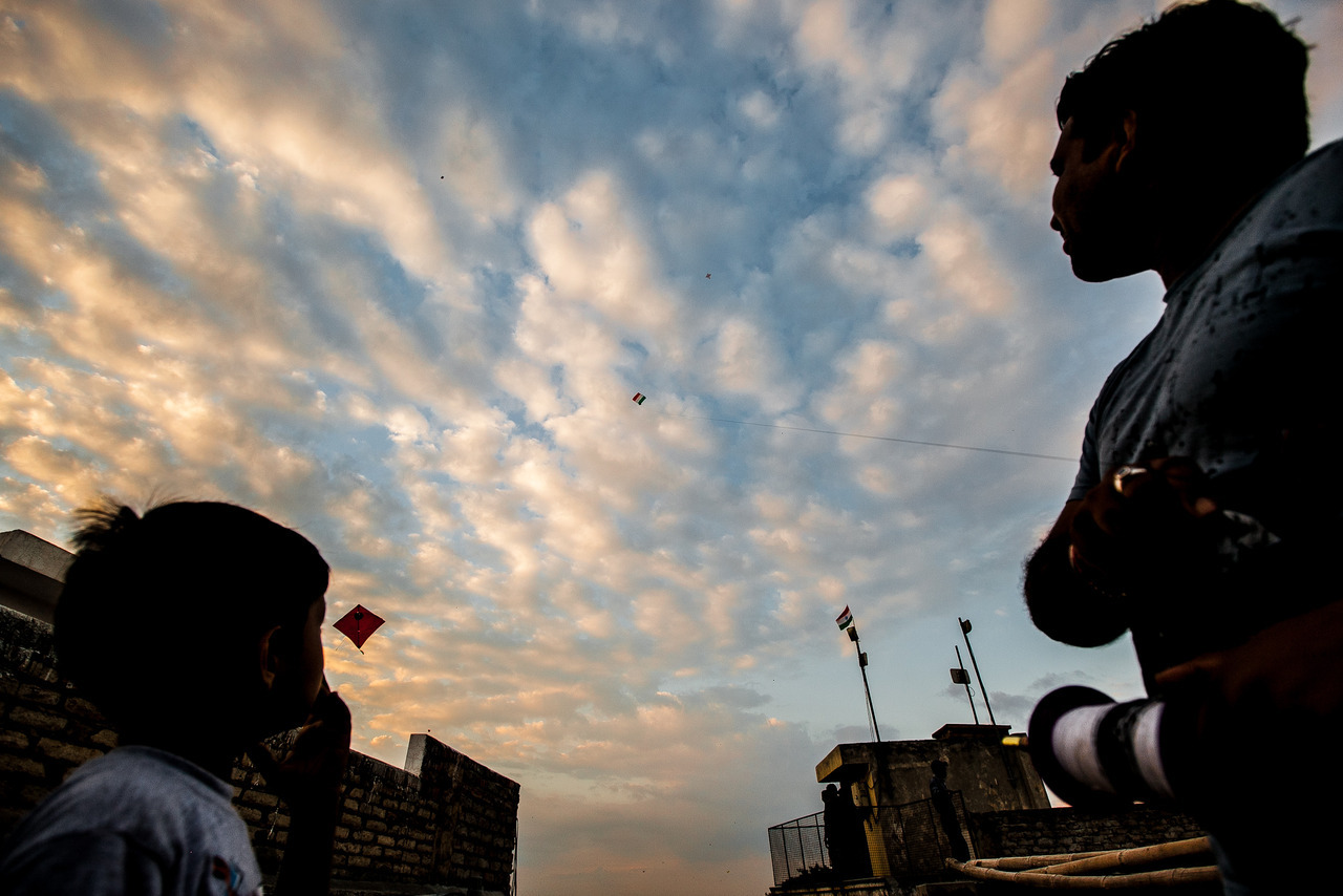 A father and son fly a kite with the Indian flag from their rooftop on Independence Day.