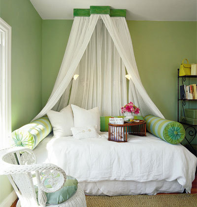 guest bedroom with a green and white fairy canopy bed