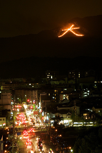 Fiery Chinese symbols appear to float above the night sky around Kyoto This iconic fire festival, marks the end of Obon, the Japanese festival of the dead More on Daimonji Gozan Okurib by Somewhere in the world today… Picture: 大文字 2008 京都五山の送り火 Gozan no Okuribi by makupo, on Flickr.