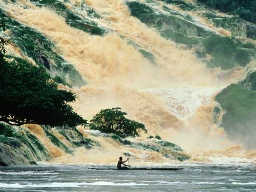 A man rows through Kongou Falls in Ivindo National Park, Gabon