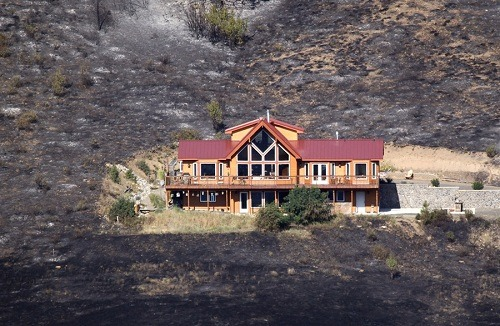 House survives encroaching wildfire in Washington Flames from a wildfire in Eastern Washington surrounded this house near Cle Elum on Aug. 14. The next day, the house was still standing, despite being surrounded by burnt brush and trees. Officials say the 22,000-acre Taylor Bridge fire is about 25% contained today. Read more from The Seattle Times.Photo: Elaine Thompson / AP