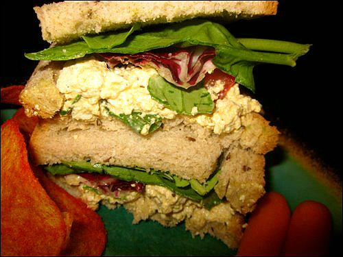 Tofu Egg-Salad Sandwich! Ingredients 1 block of extra-firm tofu, drained 1 1/2 tsp. celery seed 1/2 tsp. cumin 2 tsp. turmeric 1 tsp. black pepper 1 tsp. lemon juice 1/4 cup prepared mustard 1/2 cup Veganaise 3 1/2 Tbsp. nutritional yeast 1/2 cup chopped celery 1 cup chopped scallions 1 tomato, sliced Instructions Crumble the tofu in a large bowl-it should look like the consistency of egg salad and be a bit chunky. Add the spiced, lemon juice, mustard, Vegenaise, nutritional yeast, celery, and scallions and stir well with a spatula or fork. Make sure the tofu is covered and taste it while you stir! If you want more spices-add them! Put the tomato, lettuce, and sprouts onto the bread or into the tortilla and top with the tofu-egg salad. Volia!  Enjoy!