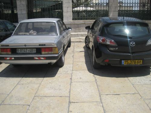 Two cars parked in Bethlehem. The one parked on the left, has a white numberplate and is owned by a Palestinian.  The car parked on the right, has a yellow numberplate, with the letters 'IL' and a small Israeli flag.  It's a strange concept - how can you know nationality of a car owner simply by looking at their licence plate?  The driver of the car with the Israeli numberplate has freedom to drive wherever their heart desires. They have the freedom of passing through checkpoints, the freedom of driving on Israeli-only roads and highways and the freedom of driving into areas where Palestinians cannot enter.  Segregated roads are just another way that Israel continues to make it difficult for Palestinians to live normal lives.  I remember riding in the car with a friend in Palestine, from her house to my hotel.  I took a deep breath in as we drove down her street - the road was so tight, I didn't feel that her car would make it.  She explained to me that the Palestinian roads were narrow, rocky and dangerous to drive on, while Israeli-only roads were constantly being upgraded and widened.  Palestinians have far less money than the Israelis, but often found themselves paying hefty fees to panel beaters - car accidents commonly occur, as the Palestinian roads are not designed to be driven on.   Another thing to note, is the standard of the cars. The Palestinian owned car is an old run-down vehicle, while the Israeli-owned car is a shiny, new imported car.  This is an indication of the economic imbalance which Israel has created - that's a whole other issue.  I still can't believe roads are segregated by race and no one is saying anything. In the west, that would be referred to as racism.