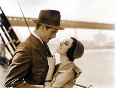 "Tough Caribbean freighter Captain Sam Whelan engages Sally Clark, a tramp masquerading as a missionary's daughter, to care for an abandoned baby on board his ship. En route to New York, ships mate Gatson sexually attacks her.  The Captain knocks Gatson overboard in an ensuing scuffle. A romance developing between the Captain and Miss Clark is put to the test in New York after an assault investigation uncovers the girl's questionable past.  -His Woman on IMDb valentinovamp:  Gary Cooper & Claudette Colbert in ""His Woman"" (1931)."