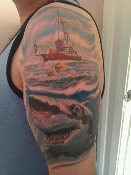 This is my dad's third tattoo. He's always been a massive Jaws fan. My dad just wanted the Jaws logo, but the artist wanted to do a whole scene.  Done by Tom Sugar of Alan's Tattoos, Moreton, Wirral, UK.