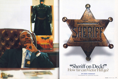 """Sheriff on Deck!"" From the article:  The sheriff in charge of the jail is a man named Victor Hill, who took office on January 1, 2005. Hill wears a pencil moustache, clock-shaped Gino Franco cufflinks that actually tell time and a badge hanging from a chain around his neck. He stands 5-feet-5. Short men with power and the lust for more are inevitably likened to Napoleon, and in his 18 months as sheriff, Hill hasn't done much to invalidate the comparison. On his first Monday in office, he summoned 27 employees to the jail on the pretense of reinstating them. Instead, he fired them. He assigned sharpshooters to watch over the proceedings as the sacked workers—most of whom had supported the outgoing sheriff that Hill had unseated—handed over their guns and badges.  Read Steve Fennessy's full feature story Flashback Friday: Victor Hill is facing 37 felony charges, but he may still win this Tuesday's runoff election and regain his position as Clayton's sheriff. Check out our 2006 feature on the man who fired 27 deputies on his first day in office, and tell us: How would you vote? Photograph by Jonathan Hollada"