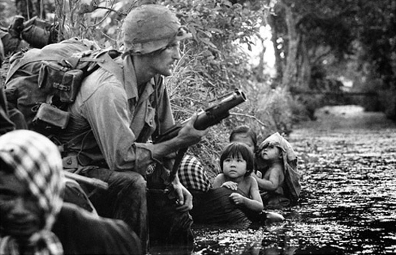 "fuckyeah13b:  This one was most likely during the Vietnam War. Showing an American G.I. taking a well deserved break in the river. Armed with what looks like an M-79 40mm Grenade Launcher affectionately known as ""Thumper"".   The M79 was designed as a close support weapon for the infantry, with two weapons being issued to each rifle squad. The tactical use of the weapon required the gunner (grenadier) to be dedicated to the weapon and only carried a pistol as a side arm. the M79 was intended to bridge the gap between the maximum throwing distance of a hand grenade, and the lowest range of supporting mortar fire - between 50 and 300 meters - and thus gave the squad an integral indirect fire weapon. With a length of 737mm (barrel = 355mm) and a loaded weight of 3kg, (6 and a half pounds) the M79 was an ideal weapon in the close terrain of Vietnam.The M79 was a single shot, shoulder fired, break-barrel weapon which fired a spherical 40mm diameter grenade loaded directly into the breech. It had a rubber pad fitted to the shoulder stock to absorb some of the shock. The M-406 40mm HE grenades fired from the M79 traveled at a muzzle velocity of 75 meters per second, and contained enough explosive within a steel casing that upon impact with the target would produce over 300 fragments at 1,524 meters per second within a lethal radius of up to 5 meters. Stabilized in flight by the spin imparted on it by the rifled barrel the grenade rotated at 3,700rpm, this in turn, after approximately 15 meters of flight, armed the grenade.For close range fighting the Army came up with two types of M79 rounds. The first was a flechette round ( or Bee Hives round) which housed approx 45 small darts in a plastic casing, these rounds were issued on an experimental basis. Later this round was replaced by the M-576 buckshot round. This round contained twenty-seven 00 buckshot which on firing was carried down the barrel in a 40mm plastic sabot which slowed down in flight so that the pellets could travel in their forward direction un-aided. The M79 could also fire smoke grenades (both standard and parachute), CS gas, and flares. The M79 had a large flip up sight situated half way down the barrel, with a basic leaf foresight fixed at the end of the barrel. The rear sight was calibrated up to 375 meters (410 yds) in 25 meter (27.3 yds) intervals. In the hands of a good experienced Grenadier the M79 was highly accurate up to 200 meters. Later in the war the M79 was superseded by the M203.   that's a lot of info, but very cool.  love the pic, always had a soft spot for black and white photos…"