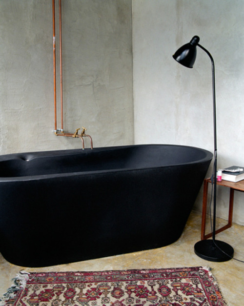 black bath, copper pipes.