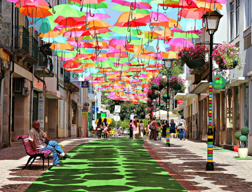 Public Space: 'Shower of colour! Artist creates illusion of floating umbrellas in vivid art installation' From Daily Mail:  Suspended from mid air these stunning colourful umbrellas certainly put other art installations in the shade. Looking as though they are floating above the ground the brollies are held in place by wires between buildings in Agueda, Portugal. The installation is an initiative by the council, in the small town just south of Porto, and is part of an art festival call Agitagueda.  Check out the rest of the photos here.