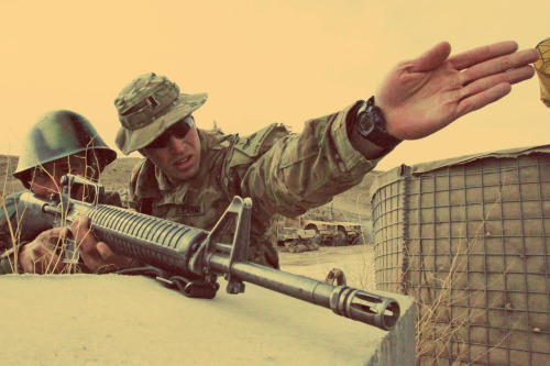 An American officer gives aiming tips to an Afghan soldier at FOB Shank, Logar province, Afghanistan. March 13, 2012.