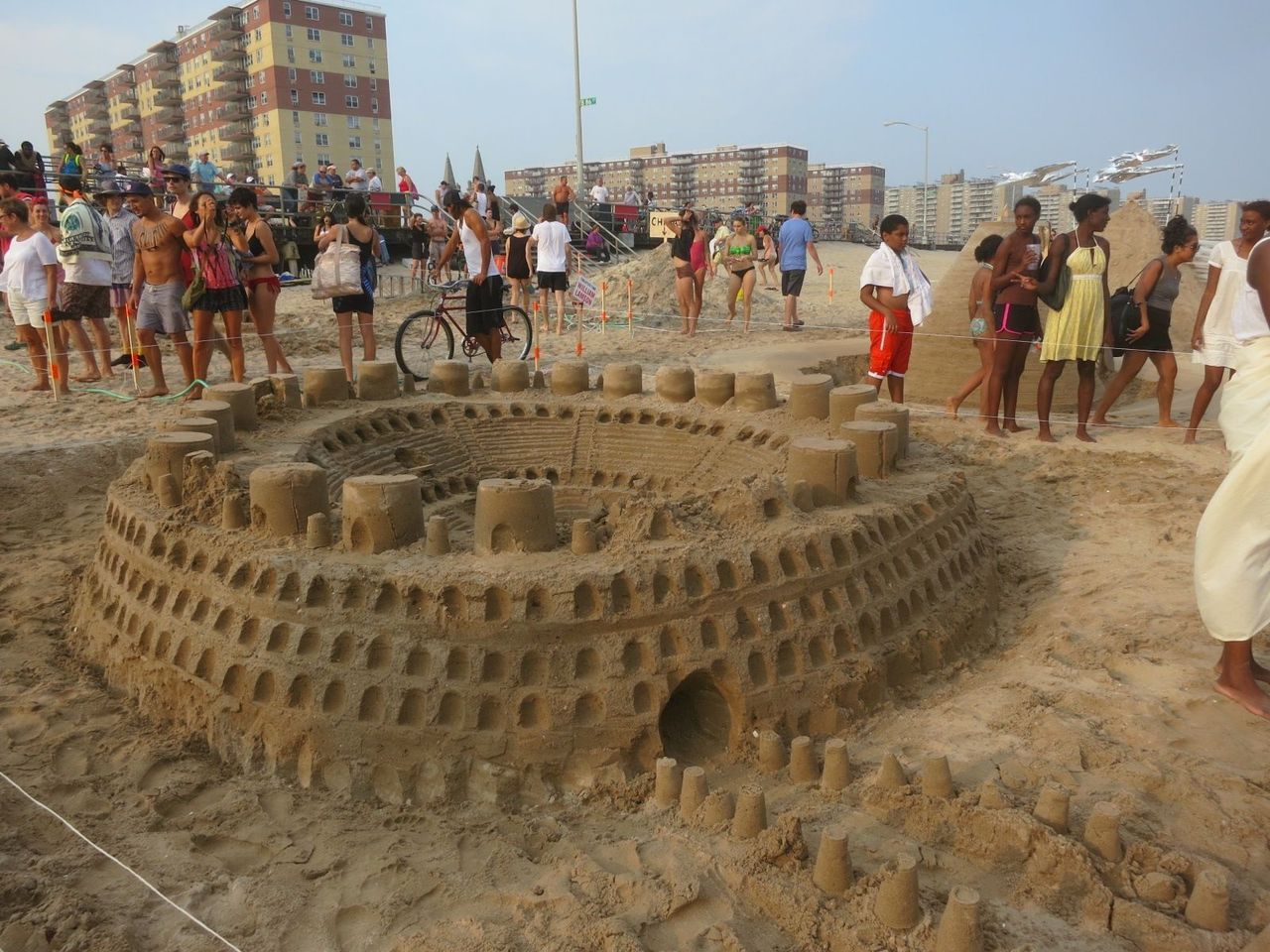 Art on the Beach!  Looks like Rome was built in a day! A sand-castle Colosseum, created by a team led by Marie Lorenz, was one of the entries in the festive artists' sand-castle competition staged by last Friday by the public-art organization Creative Time, in collaboration with Grey Area.  By mid-afternoon, a parade of artists bearing bizarre materials had materialized on Beach 86th Street, intriguing passersby as they began digging holes, building piles, burying their colleagues, and tenderly sculpting the beach's distinctive dusty grains of sand into ambitious, elaborate, and often whimsical concoctions that celebrated this venerable vernacular tradition. I was among the judges who faced the challenge of awarding prizes to the most impressive entries. We gave top honors to Jen Catron & Paul Outlaw for their Fountain. This castle was a whimsical structure on which the artists' team posed with a neo-vaudeville flourish, spouting Poland Spring water from their mouths in a deadpan manner that recalled everyone's favorite Baroque sculptures (with a sly wink to Bruce Nauman's sly wink to modernism's most famous Fountain, by Duchamp).    Second went to William Lamson for a huge, flawless cone, a kind of grown-up version of those rickety turrets kids make with plastic cups—though the artist noted that his inspiration also came from the elegant post-Minimalist forms of Japanese Mono-ha.  And third went to Jen DeNike for Castles in the Sand, a female form that seems to spring out of a dream (and a Hendrix song) onto the sand, reaching for an elusive structure destined to fall into the sea.  There were a lot of other striking pieces, including Tom Sachs' dig to almost-China and Ricci Albenda's pyramidlike wall with a slight Ozymandias complex.   By now, all of the sculptures have been blown away, trampled by dogs, and reconstituted by seagulls. But I wouldn't be surprised if their influence lingers in the air. Look for their echoes on the shore—and for the next round of entries next year!   Photo: Mista Oh!
