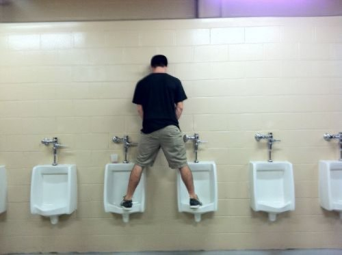 Guy Stands on Urinals Don't worry, with practice you'll figure it out.