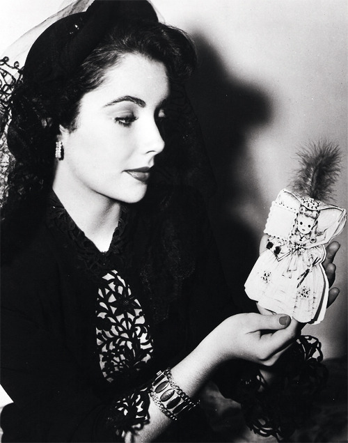 Elizabeth Taylor holding a Hallmark greeting card with feather plume in the likeness of her role as Amy in Little Women