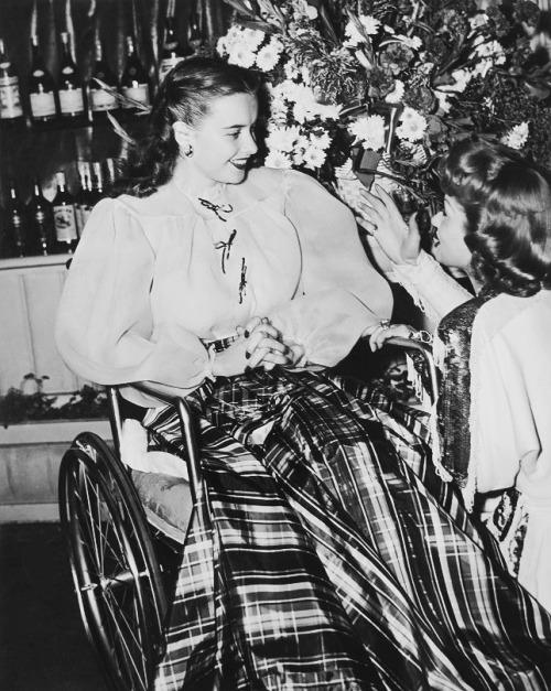 Lucille Ball chatting with a girl who's in a wheelchair, 1946