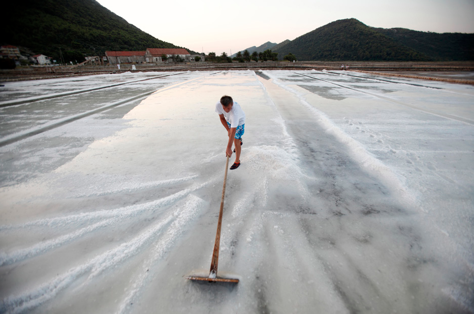 A worker collects salt at the Ston Saltworks site in Ston, south Croatia, July 31, 2012. The Ston Saltworks at the oldest and best preserved salt works from Mediterranean history, with technique dating from the time of the Republic of Dubrovnik. As the production method has not changed from the manual salt production in the Middle Ages, the salt works have become a tourist attraction. Salt at Ston Saltworks is gathered bt locals and volunteers every summer between July and September. REUTERS/Antonio Bronic