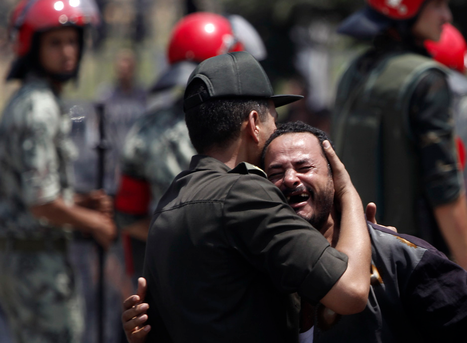 A member of the Army embraces a relative of one of the soldiers killed during an attack at a checkpoint along the Sinai border with Israel by unknown gunmen, during their funeral at the tomb of the late President Anwar al-Sadat and the Unknown Solider monument in Cairo August 17, 2012. REUTERS/Amr Abdallah Daish