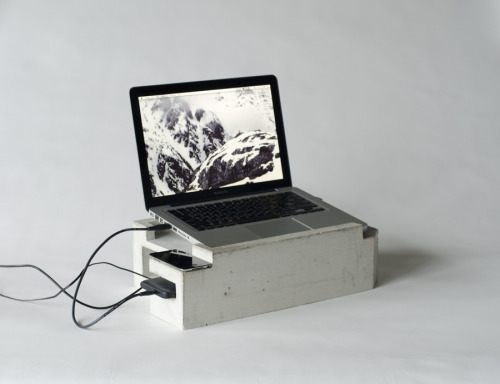 "'Foundation' by Greg Papove (2008)This laptop stand gives your take-anywhere-computer a home base. Inspired by housing foundations it is made of concrete and created using forms similar to full-scale housing construction. It fits a 13"" MacBook, external hard-drive, iPod, and Cellular phone."