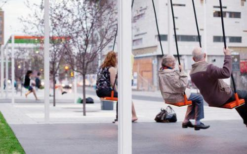 """A bus stop with swings! Except the truth is even better. This is in Montreal and every summer they put up a series of musical swings. If you look in the background you can see more people swinging away. Each swing is a set of four and has its own unique sound, but if you are in perfect harmony with the other 3 seats then an actual song is played. The theory is that you communicate and interact with people more if it's for a specific goal and if you're having fun."""