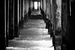 Black and white perspective under the pier at Coney Island.