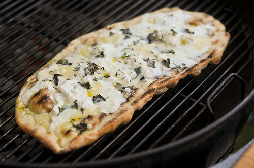 culinaryconfessional:   Grilled White Pizza   1 (8-ounce) ball pizzeria or frozen from market) 2 tablespoons extra-virgin olive oil, plus more for drizzling Salt and freshly ground pepper 1 cup grated Parmesan 1/4 teaspoon red pepper flakes, or more to taste 1 tablespoon finely chopped fresh oregano leaves Fresh basil leaves, for garnish Directions Heat grill to high. Roll the dough into 2 (10-inch circles). Brush with olive oil and season with salt and pepper. Transfer dough to grill. When bottom side is mostly cooked through, brush with 2 tablespoons olive oil and sprinkle evenly with grated cheese, red pepper flakes, oregano, and salt and pepper. Let cook until dough is cooked through and slightly charred. Remove from grill, garnish with fresh basil, and cut into pieces.Approximate Nutritional Values: http://www.food.com/recipe/grilled-pizza-367466