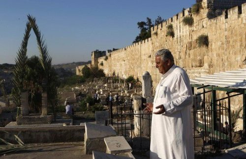 A Palestinian man prays next to a grave at a Muslim cemetery just outside Jerusalem's Old City on the first day of Eid al-Fitr, which marks the end of the holy month of Ramadan, August 19, 2012. (REUTERS/Baz Ratner)