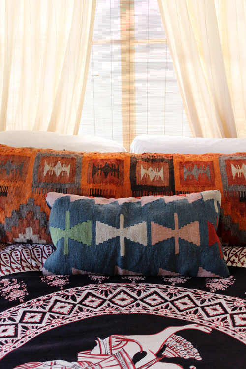 I love the idea of a mixed-and-matched bed. Differently patterned pillows, sheets, comforters, and blankets within the same color scheme is a fun way to bring color into a room and keep it cozy. Though I love cleanliness and orderliness, sometimes you just want the comfort of tons of pillows and blankets without having to worry about what's in order or if the shams match the comforter. Bedrooms should be warm and inviting! (Or at least that's what I think.)