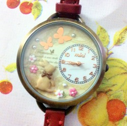 childofmotherearth:  This watch was so cute I couldn't resist buying it :). It's brass on the sides, a pretty design within: bunny, butterflies, flowers, and pearls. It also has maroon strap and brass clasp. It's just so cute!