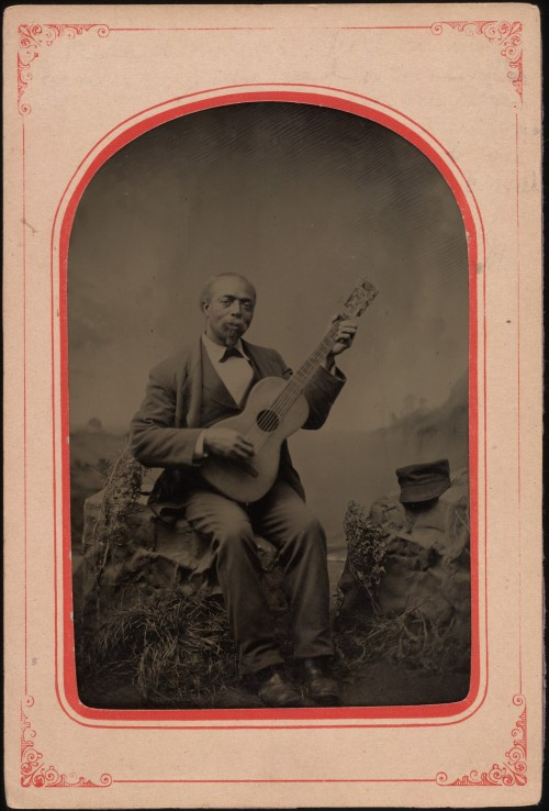 ca. 1885, [tintype portrait of a gentleman playing his guitar with a slight smile] via Yale Collection of American Literature, Beinecke Rare Book and Manuscript Library, Randolph Linsly Simpson African-American Collection