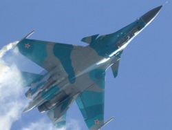 Sukhoi Su-30 showing off. Man, those vertical stabilizers make the jet.  The Sukhoi Su-30 (Cyrillic: Сухой Су-30; NATO reporting name: Flanker-C) is a twin-engine, two-seat supermaneuverablefighter aircraft developed by Russia's Sukhoi Aviation Corporation. It is a multirole fighter for all-weather, air-to-air and air-to-surface deep interdiction missions. The Su-30 started out as an internal development project in the Sukhoi Su-27 family by Sukhoi. The design plan was revamped and the name was made official by the Russian Defense Ministry in 1996. Of the Flanker family, only the Su-27, Su-30, Su-34 and Su-35 have been ordered into serial production by the Defense Ministry. All the others, such as Su-37, were prototypes.  info from wiki.