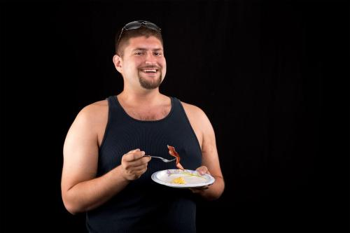 Man laughing alone with bacon.