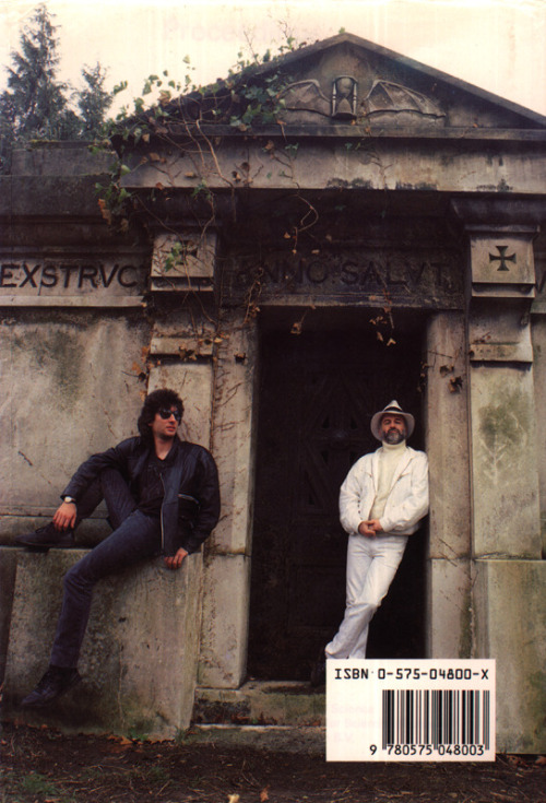 """neil-gaiman:  nothingbutthedreams:  I just rediscovered how glorious this image is so excuse me while I laugh uncontrollably every time I look at it again.  It was taken in Kensal Green Cemetery in February. Terry borrowed the white jacket from our editor, Malcolm Edwards, and grumbled that it did nothing to keep him warm on a very cold day. """"Sometimes you have to be cold to look cool,"""" I told him. """"It's all right for you,"""" he said. """"You're wearing a leather jacket."""" """"You could wear a leather jacket too."""" """"I'm wearing white,"""" said Terry, pointedly. """"That way, when they come after us for writing a blasphemous book, they'll know I'm the nice one."""" (After the photo was taken we noticed the bat-winged hourglass, which we hadn't seen during the photo session, and requested bat-winged hourglasses as a design motif in the book.)  Two of our favorites, looking awfully sharp on the back cover of Good Omens…"""