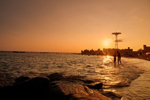 "Coney Island beach at sunset. Brooklyn, New York City.  The sun whispers to the ocean in golden-voiced tones on evenings like these.  Summer's warmth falls onto the bare skin of the earth as the air is punctuated by the sounds of distant laughter and birds.  And the city fades into the haze like a nostalgic thought carried away by an all too familiar melody.  —-  I had a bit of a camera tragedy a few weeks back. My beloved Sony SLT-A55 stopped working.  It's currently being looked at by Sony and I have had the pleasure of using a Sony SLT-A77 (the image in this post was taken with it) as a loaner camera until the end of the month which has been nothing short of magical. I plan on doing a write-up later this week regarding how the Sony SLT- A55 compares to the Sony SLT- A77.     —-   View this photo larger and on black on my Google Plus page  —-  Buy ""Beach Sunset - Coney Island - Brooklyn - New York City"" Prints here, email me, or ask for help."