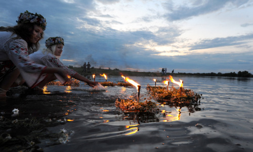 Belarusians place candles in the river while celebrating Ivan Kupala, the feast of St. John the Baptist, a traditional Slavic orthodox holiday celebrating the summer solstice, 270 kilometers south from Minsk in Turov early on July 7, 2010. AFP PHOTO / VIKTOR DRACHEV (Photo credit should read VIKTOR DRACHEV/AFP/Getty Images) Photo by On Being