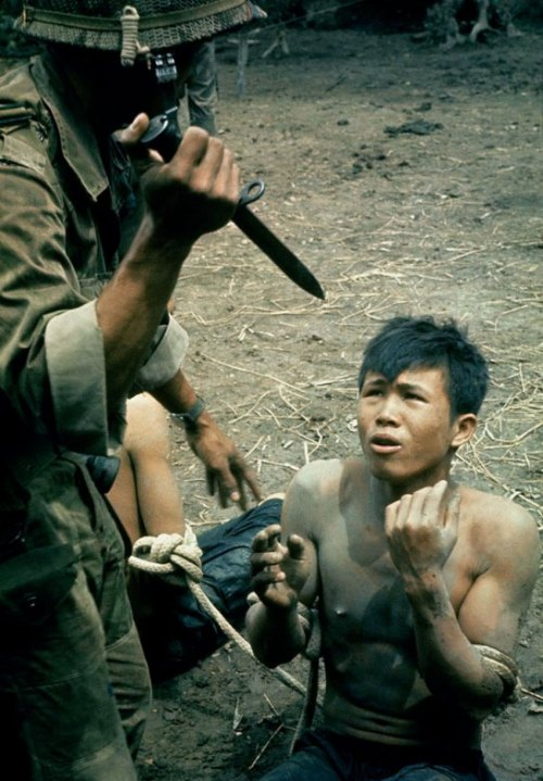 "Vietnam 1963: ""A captured Viet Cong kneels in terror as Vietnamese guard threatens him with bayonet.""  Photo by Larry Burrows for Life magazine. (LIFE)"