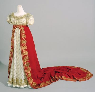 """This dress and its train (known in French as a queue de cour) were worn by the wife of the Conseiller d'Etat, Jean Bérenger (1767-1850) (Comte de l'Empire in 1808), during the ceremony of the coronation of Napoleon I. The dress is in ivory silk, delicately embroidered with silver and gold thread. On the shoulders there are small embroideries in ivory tulle. The train is made of scarlet velvet silk with a lining of white satin. This ensemble was kindly loaned by the owner for the exhibition at the Musée Jacquemart-André, 'The Treasures of the Fondation Napoléon', 28 September, 2004, to 3 April, 2005."" c. 1804 © Fondation Napoléon - Patrice Maurin-Berthier"