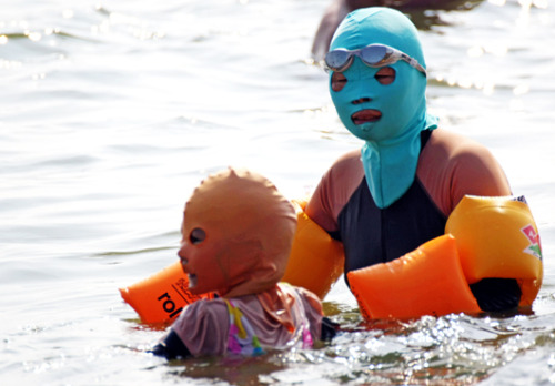 "mothernaturenetwork:  'Facekinis' take China by stormA parent and a child wear body suits and protective head masks — dubbed ""facekinis"" — on Aug. 16 while swimming at a public beach. Although a nice tan is desirable in many cultures, it's not in China, where people regularly carry umbrellas — not to shield from the rain, but from the sunlight. In an agricultural society like China, tanned skin traditionally implies that one works outside all day in the fields, while lighter skin implies wealth and a higher social status. Initially designed to protect the wearer from sunburn, the unusual swimming mask is also effective at repelling jellyfish and insects."