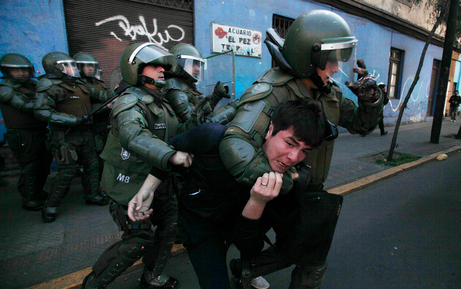 A student is detained by riot police during a demonstration against the government to demand changes in the public education system in Santiago, August 8, 2012. REUTERS/Carlos Vera